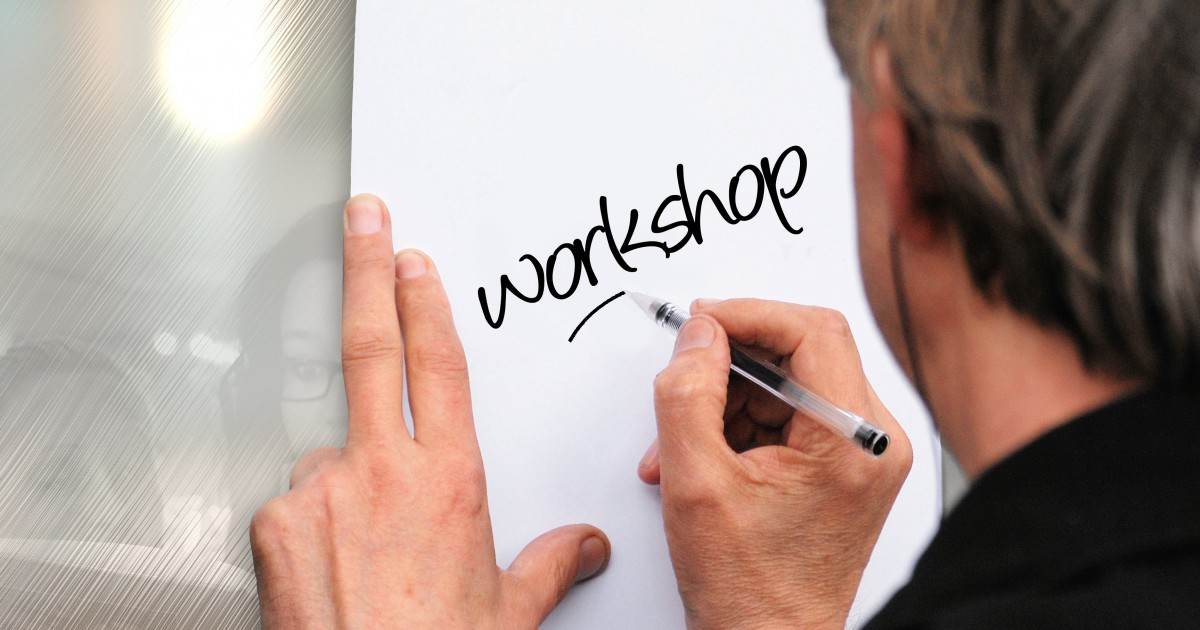 Man writing workshop on a piece of paper in black marker