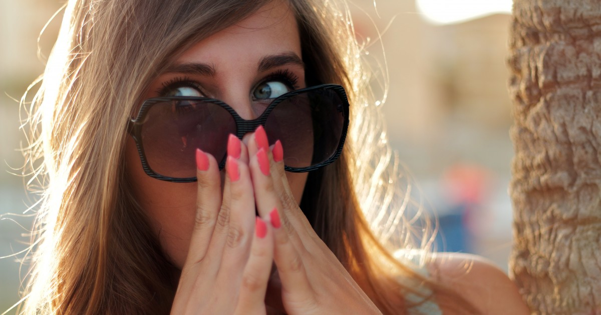Suprised woman with pink painted fingernails and hands to her face