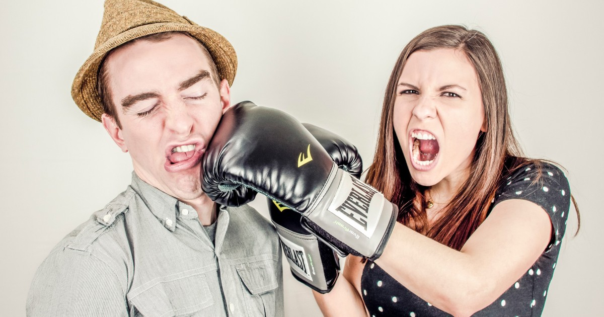 Funny picture of lady punching a guy with a boxing glove