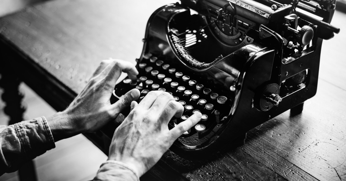 An old fashioned typewriter with hands typing