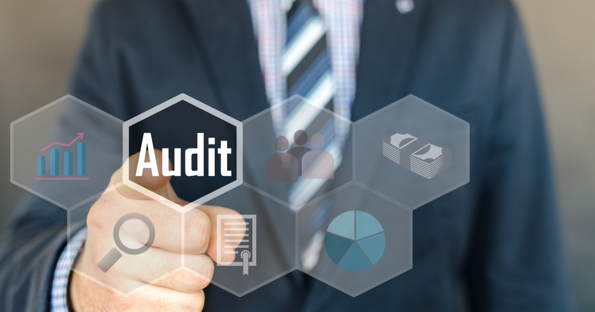 Man pointing toward the word audit in a virtual interface