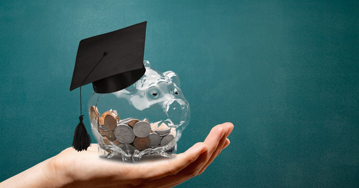 Partially full glass piggy bank with graduation cap, being held in an outstretched hand